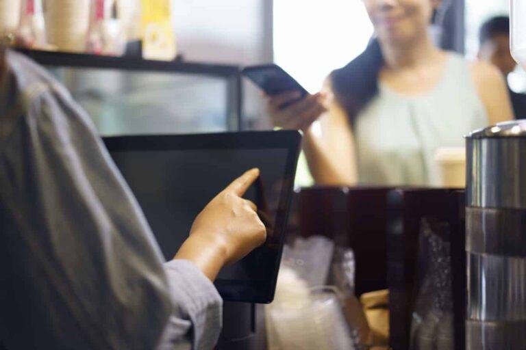 Customer using smart phone whilst ordering